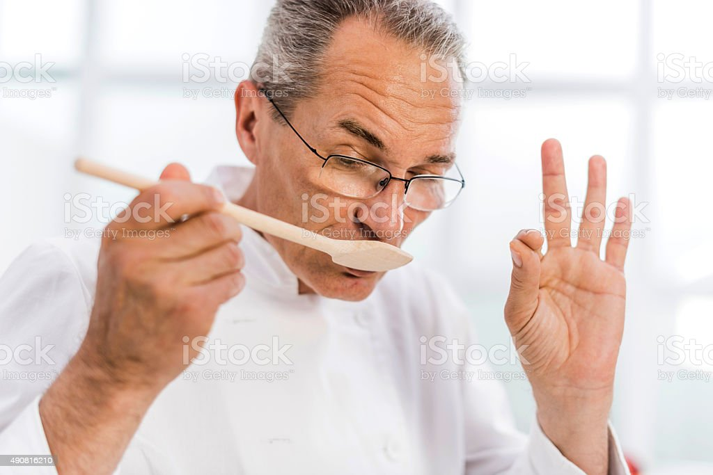 Chef tasting food and showing OK sign. stock photo