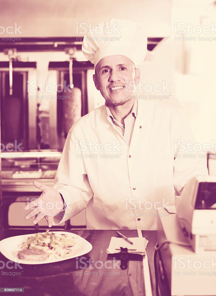Chef wearing uniform standing near plate with  kebab stock photo