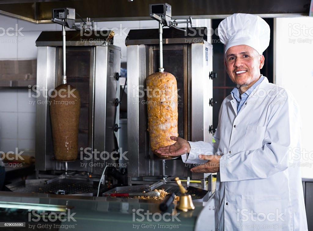Chef wearing uniform standing on kitchen stock photo