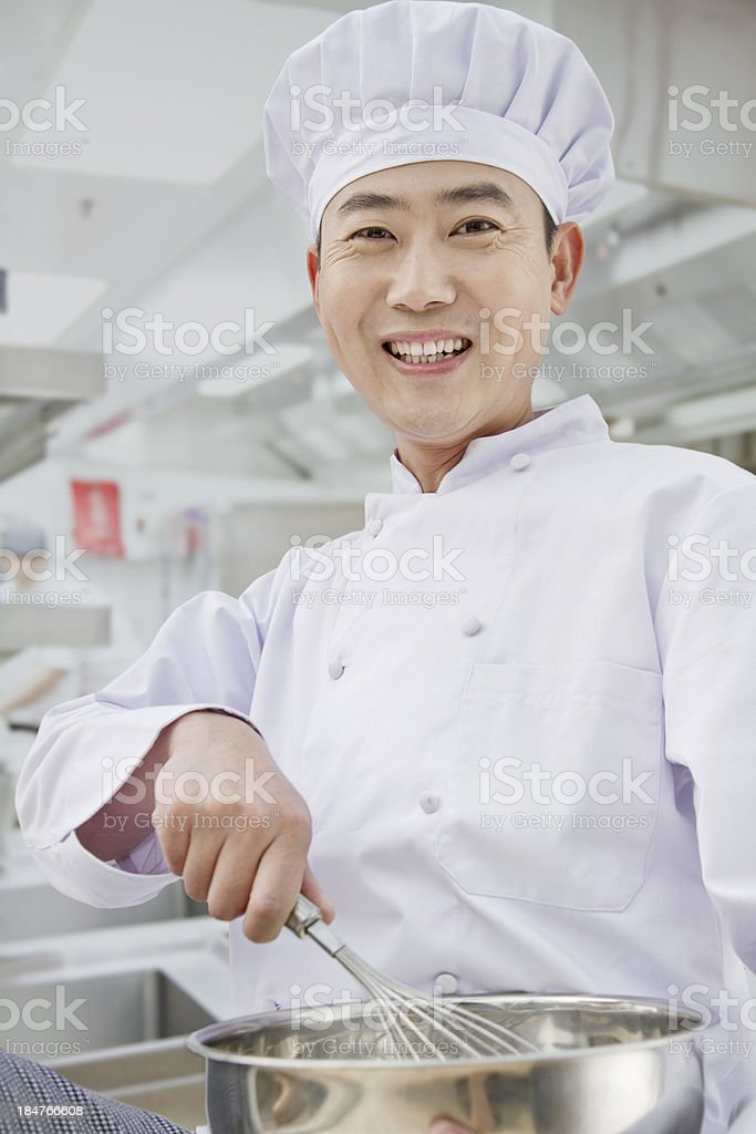 Chef whisking in bowl, portrait stock photo
