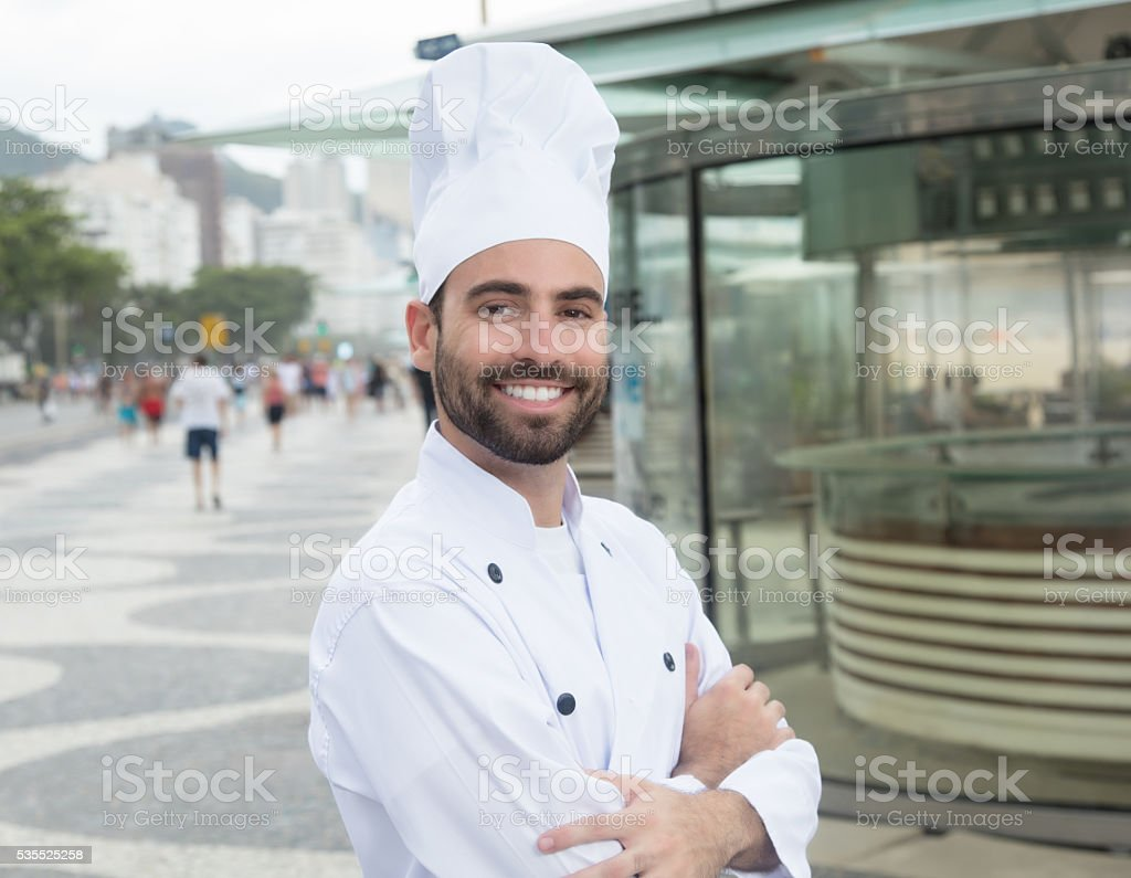 Chef with beard and crossed arms in front of restaurant stock photo