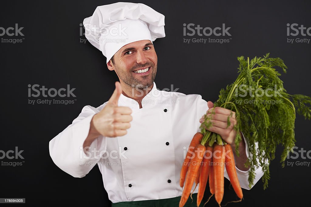 Chef with bunch of carrots showing thumbs up royalty-free stock photo