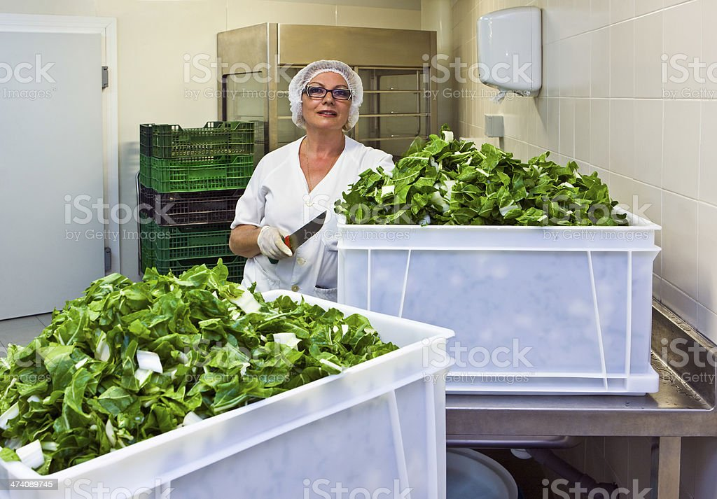 Chef With Cut Leafy Vegetable In Hospital Kitchen stock photo