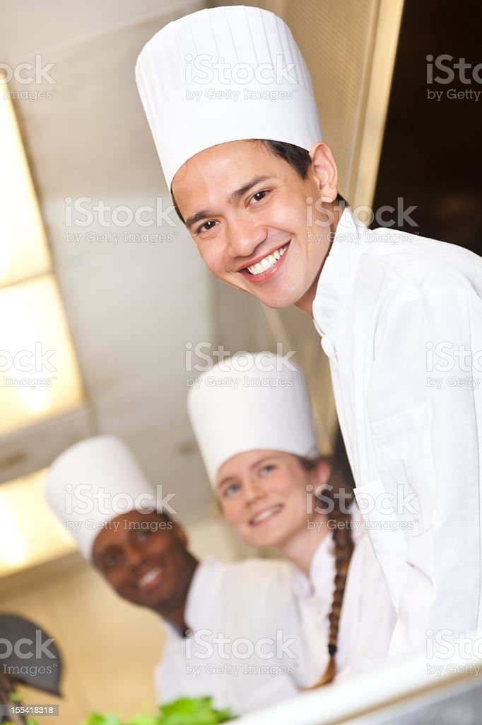 Chef with fellow chefs working in the restaurant kitchen royalty-free stock photo