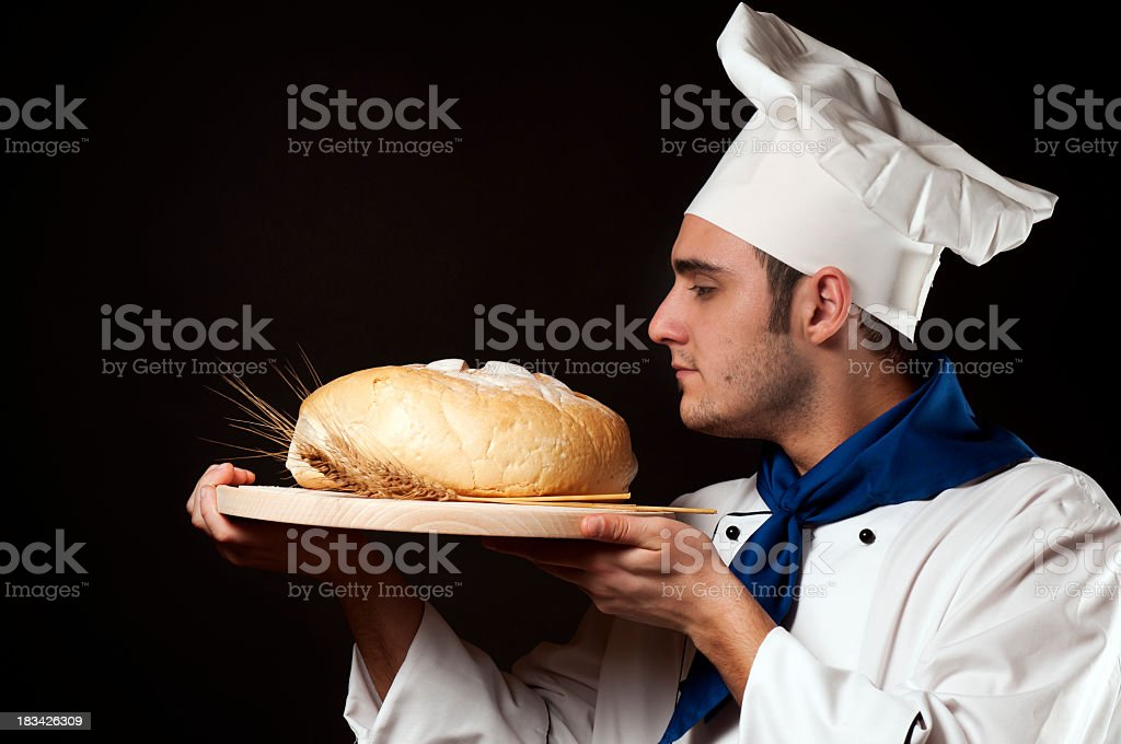 Chef with fresh bread, isolated on black royalty-free stock photo