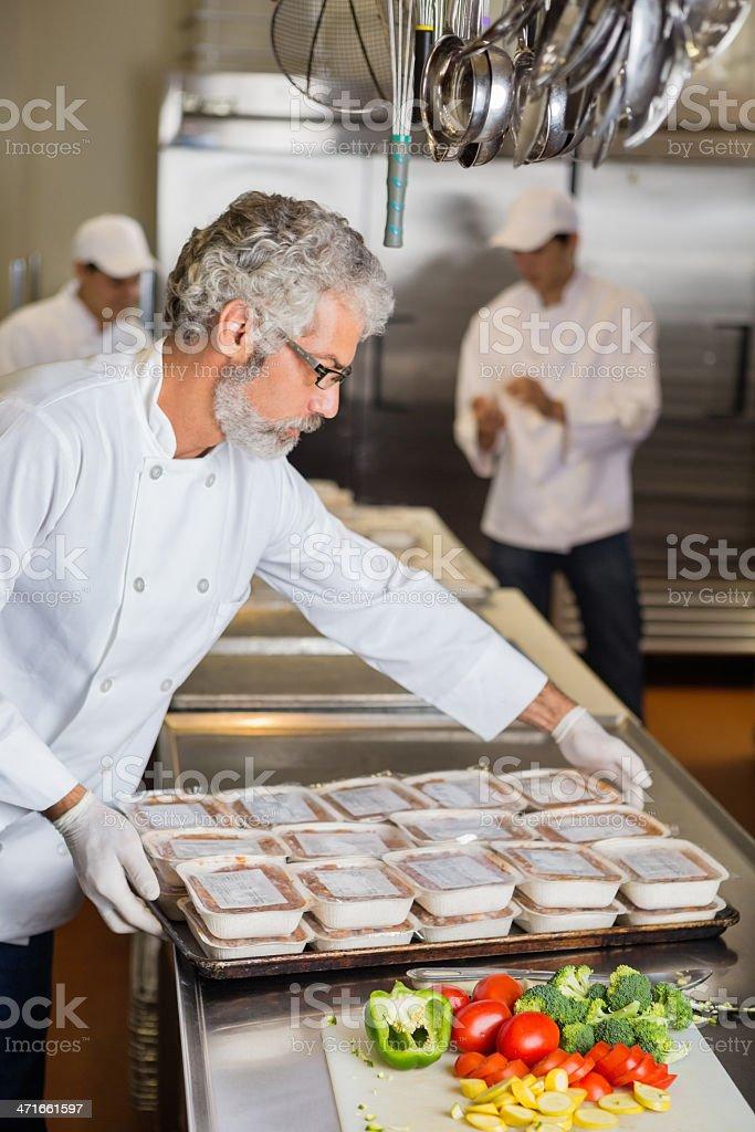 Chefs volunteering to prepare frozen meals for food bank stock photo