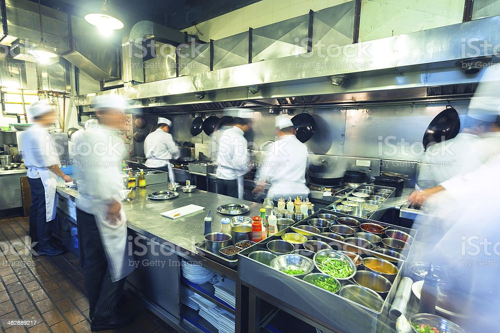 Chefs Working Busily in Chinese Kitchen stock photo