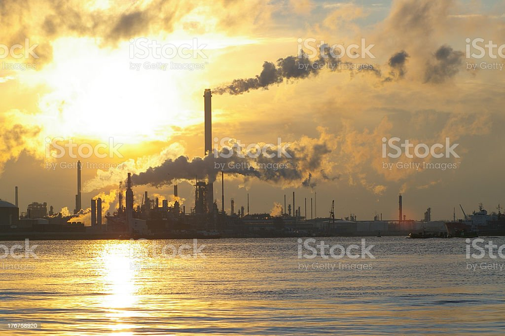 A chemical plant across the water giving off smoke royalty-free stock photo