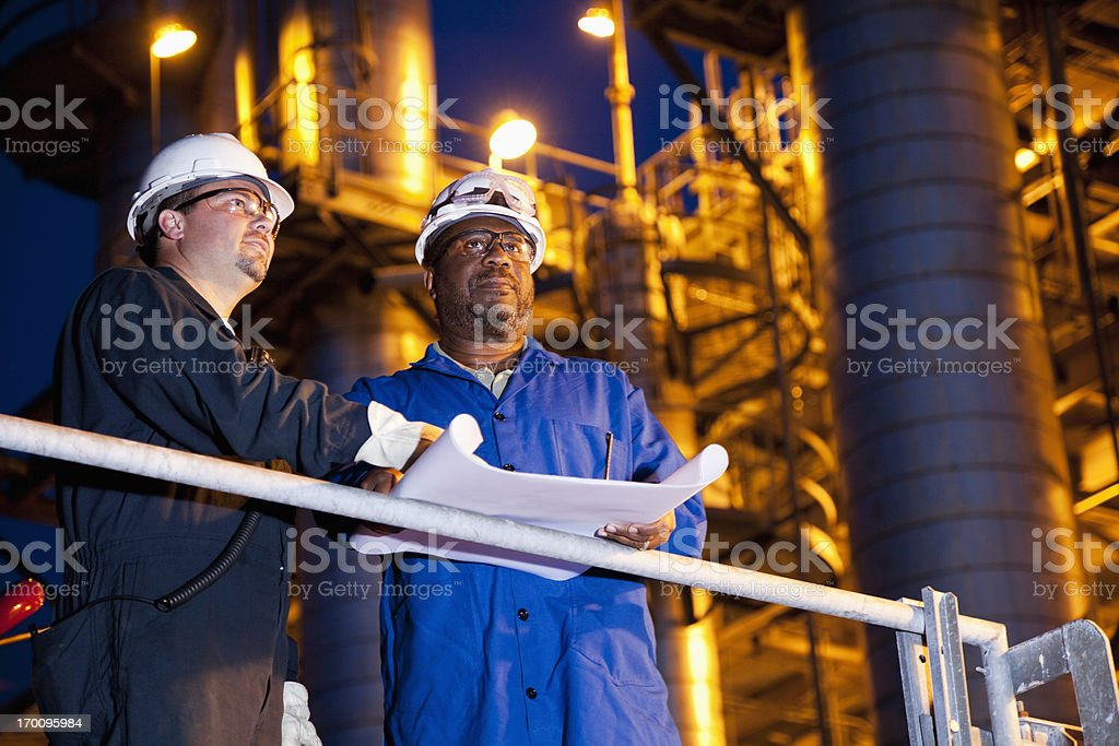 Chemical plant workers at night stock photo