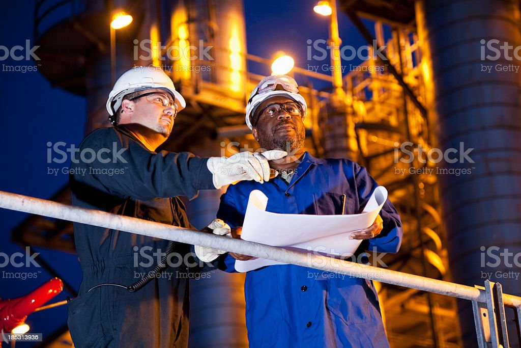 Chemical plant workers at night royalty-free stock photo
