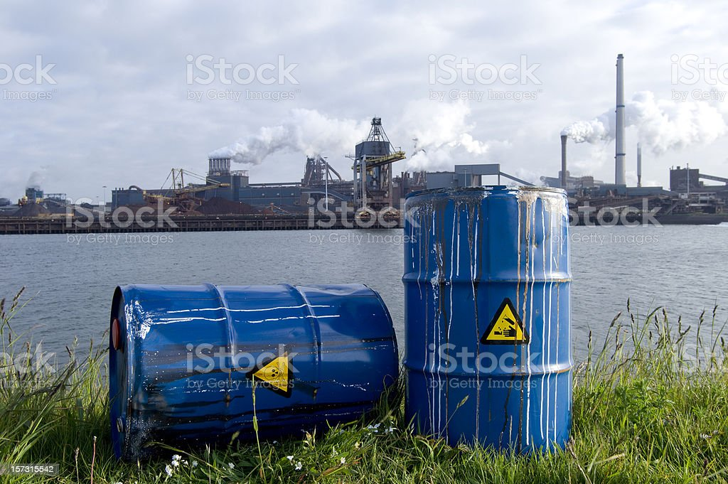 chemical waste drums in front of heavy industry stock photo