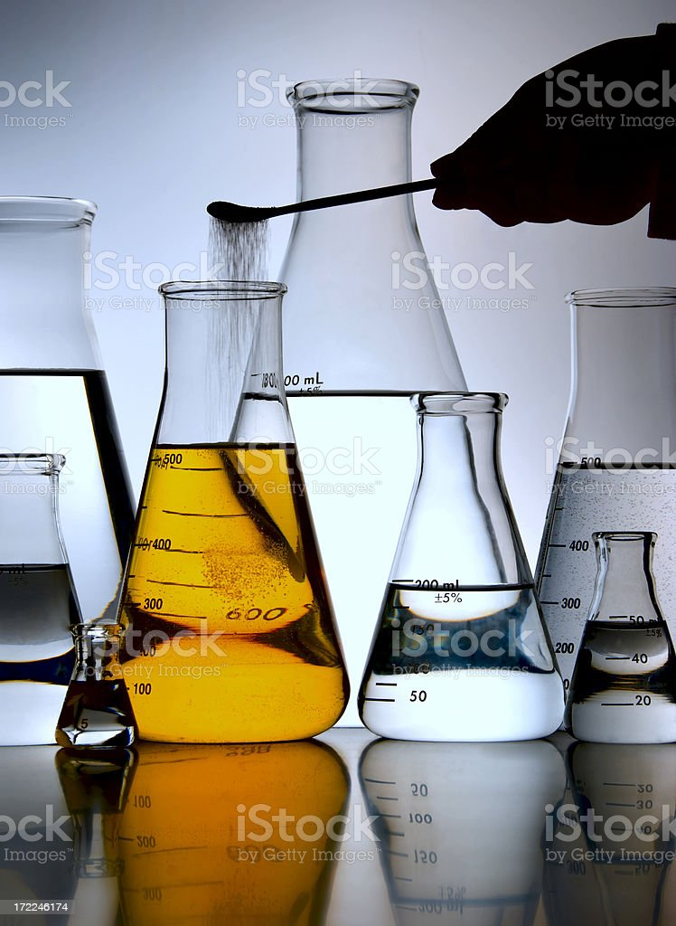 Chemist Adding Powder to Laboratory Flask with Yellow Chemical Solution royalty-free stock photo