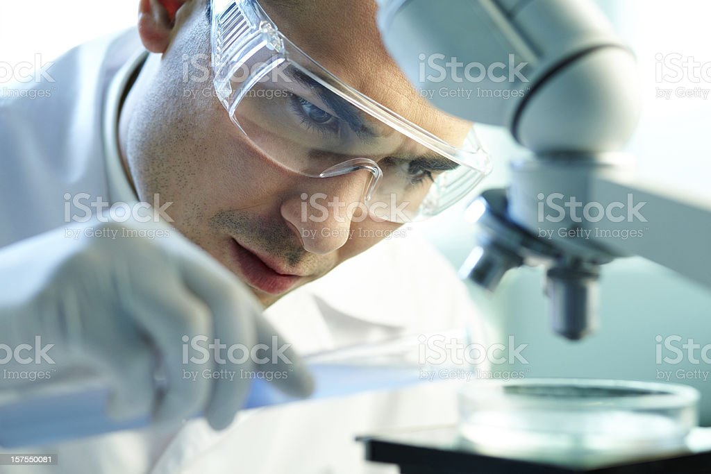 Chemist at work wearing protective glasses and gloves royalty-free stock photo