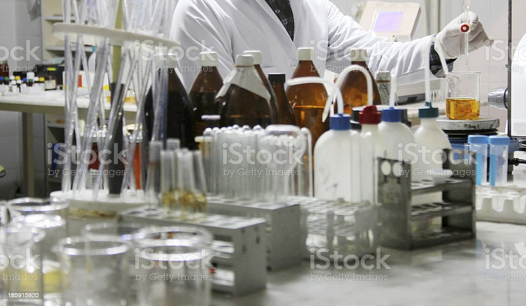 A chemist experimenting in a laboratory full of chemicals royalty-free stock photo