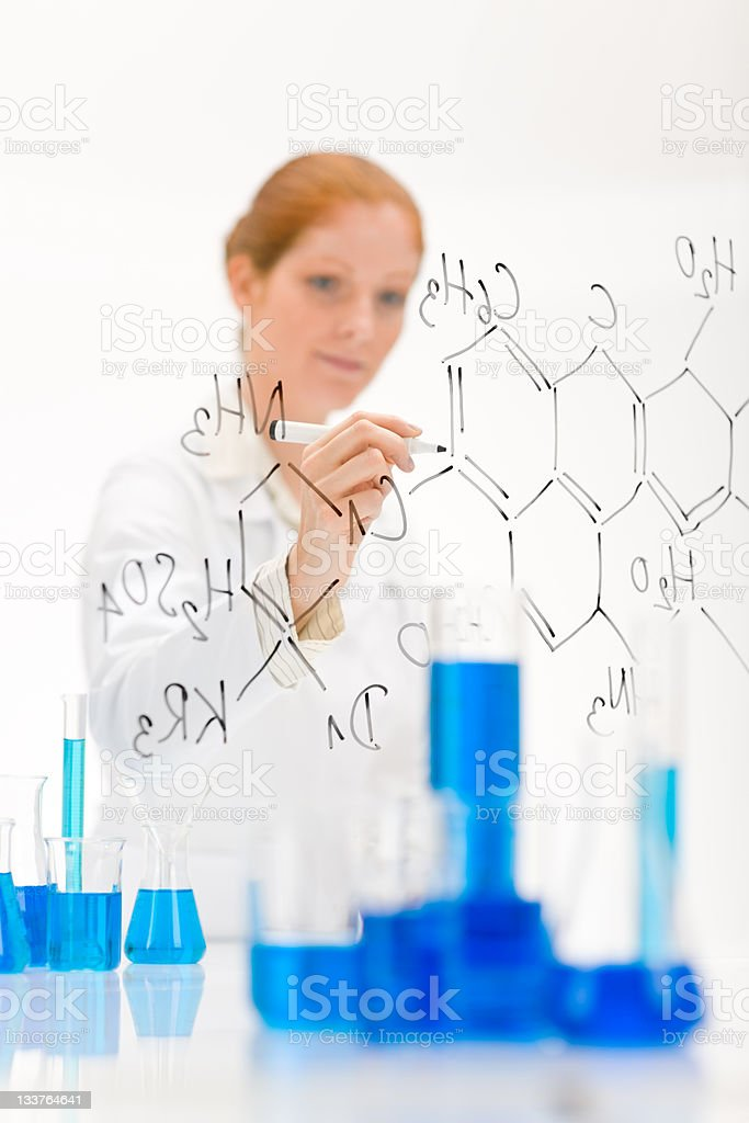 Chemistry experiment - Woman scientist in laboratory write chemical formula stock photo