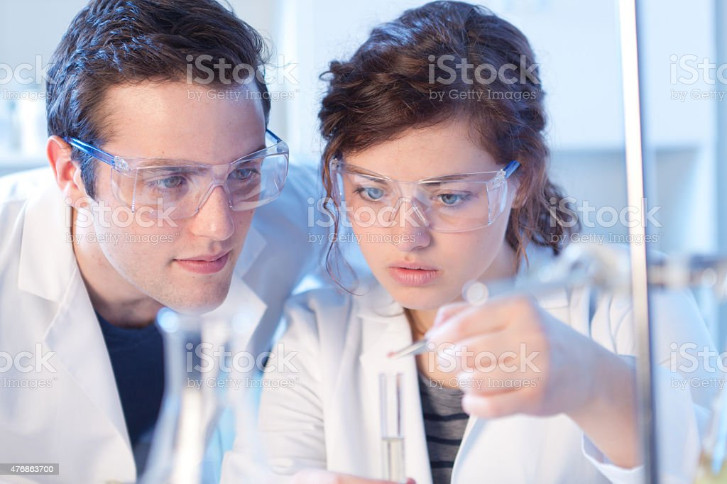 Two chemistry laboratory researchers or students, a young man and a...