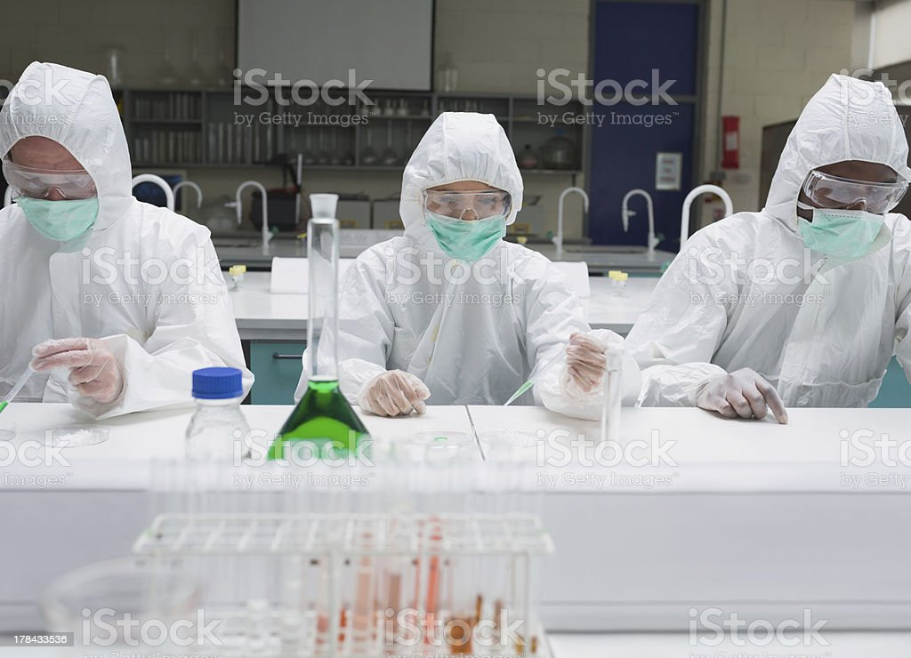 Chemists working in protective suits royalty-free stock photo