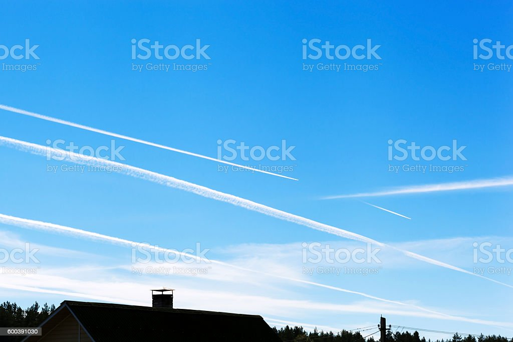 Chemtrails on blue sky stock photo