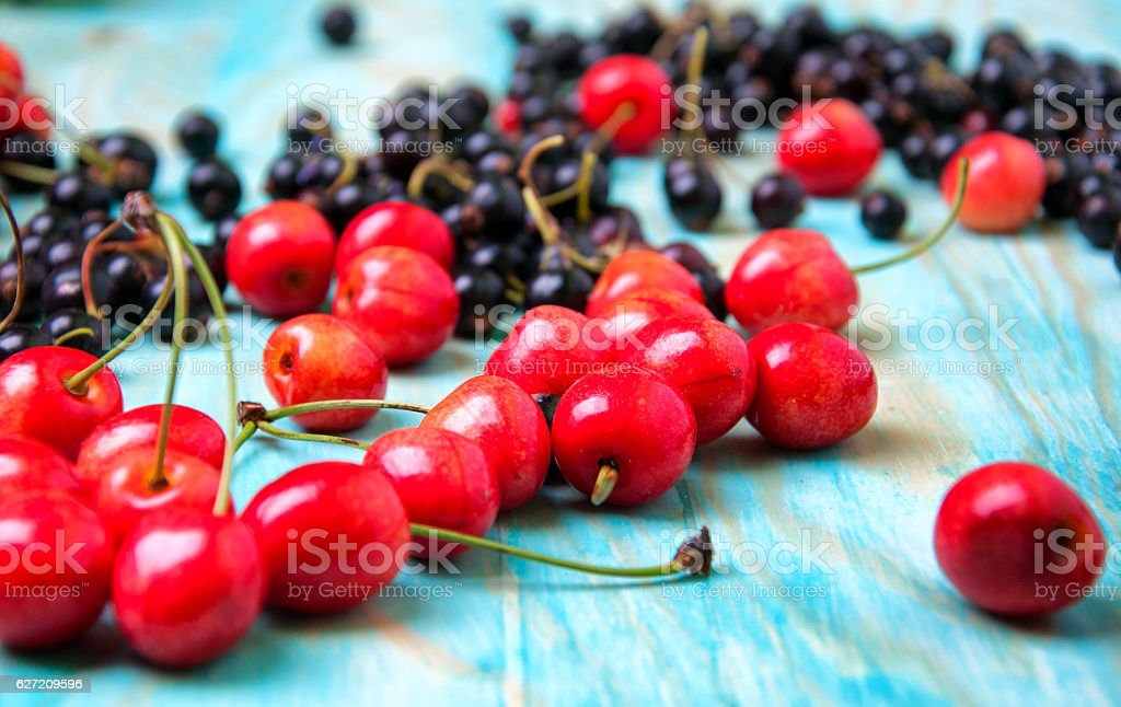 Cherries and currants on blue wooden background stock photo