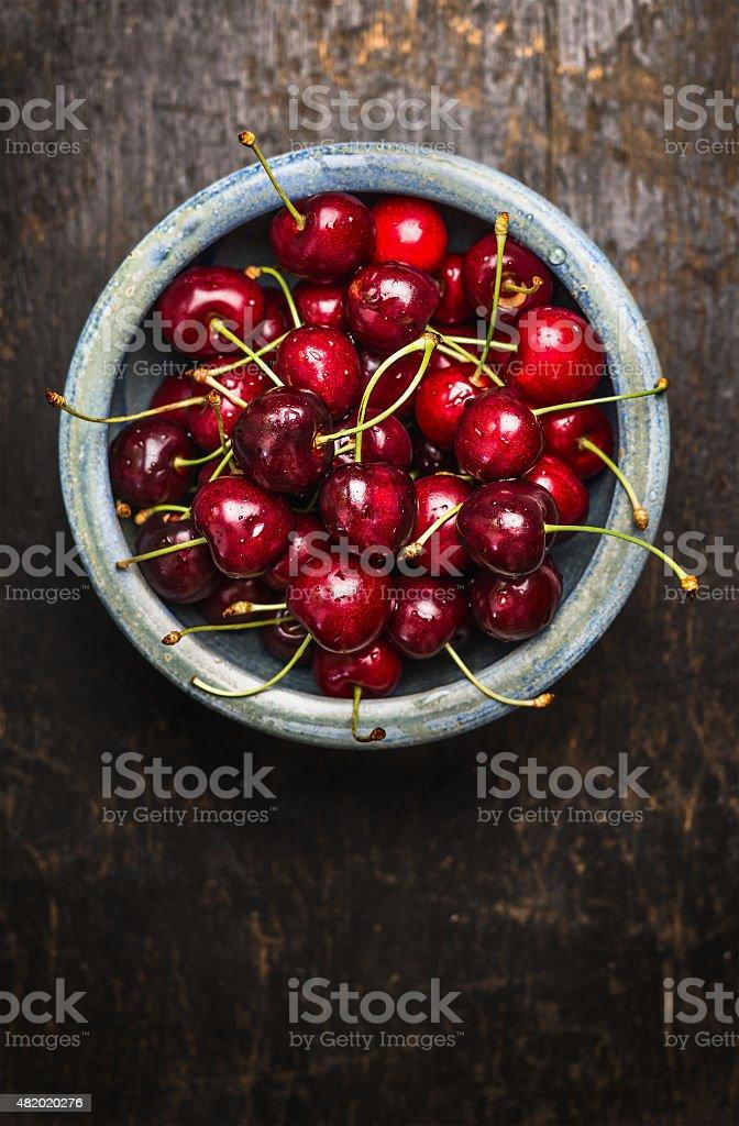 Cherries berries in blue bowl on dark rustic wooden background stock photo