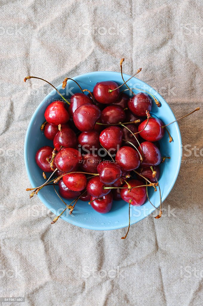 Cherries in blue bowl, flat lay stock photo