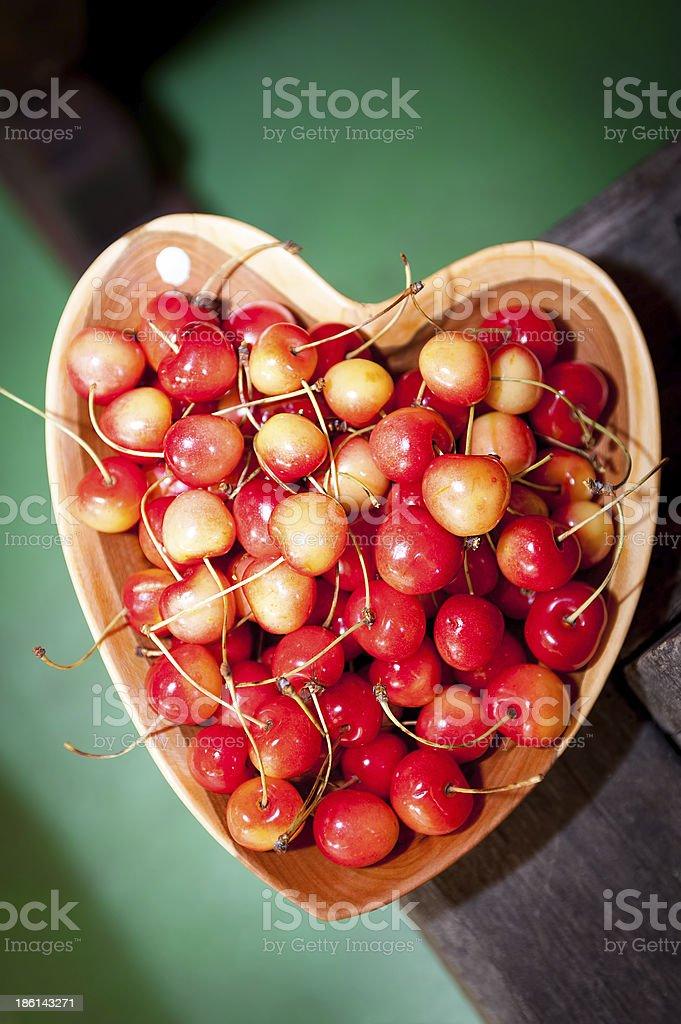 Cherries in heart shaped clay dish stock photo