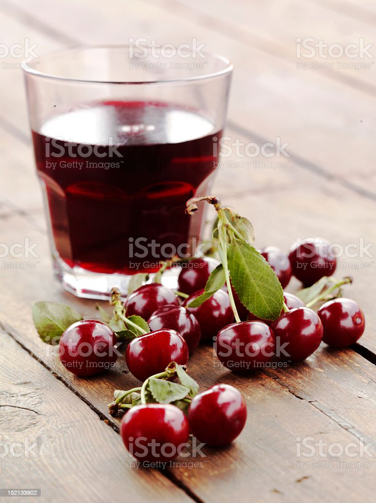 Cherries in original and liquid form set on a wooden table stock photo