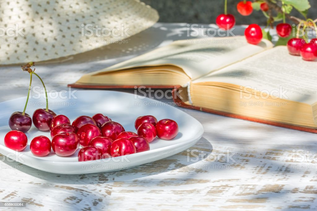 Cherries on a plate, a hat and the book, close-up stock photo