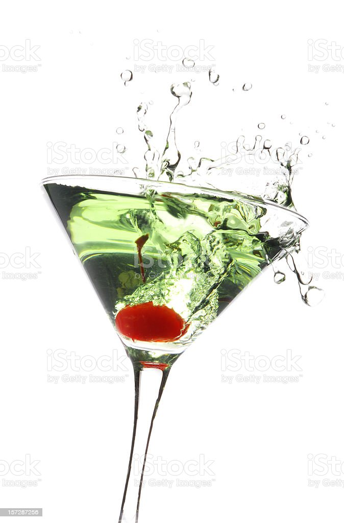 Cherry being dropped in a green apple martini stock photo