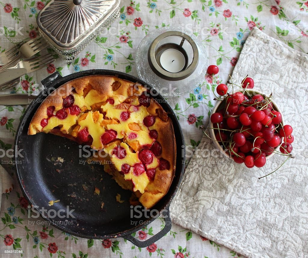 Cherry clafoutis in skillet with fresh cherries on linen stock photo