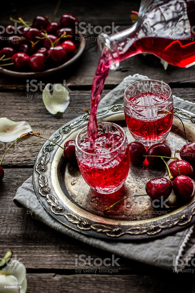 Cherry homemade liquor flowing in a vintage glass. stock photo