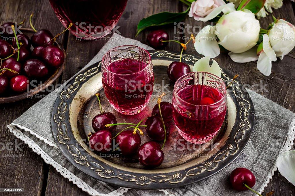 Cherry homemade liquor on metal tray and cherries stock photo