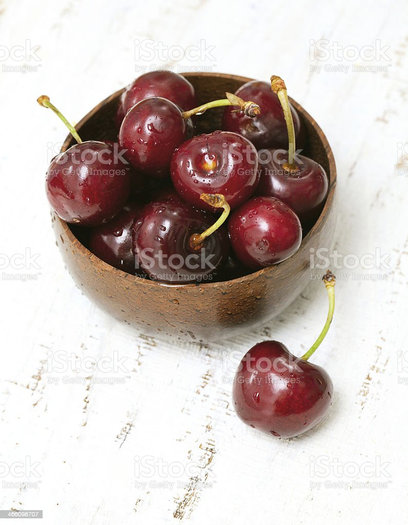cherry in a bowl on wooden surface royalty-free stock photo