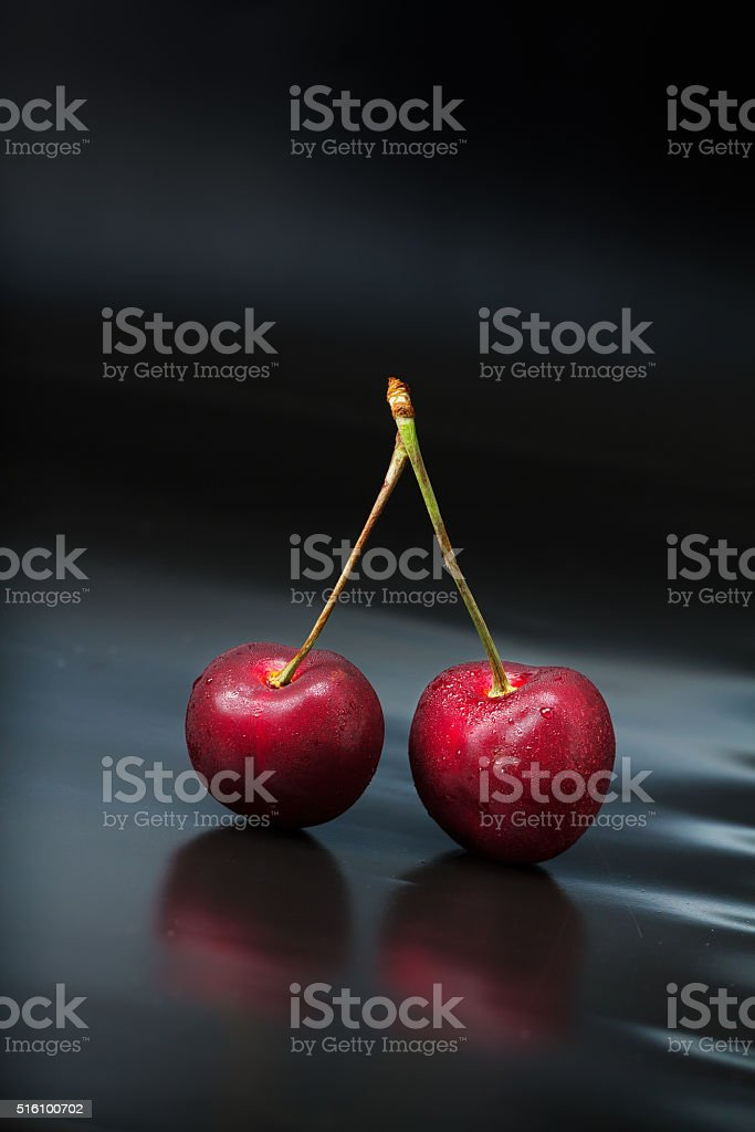 Cherry on black reflective background stock photo