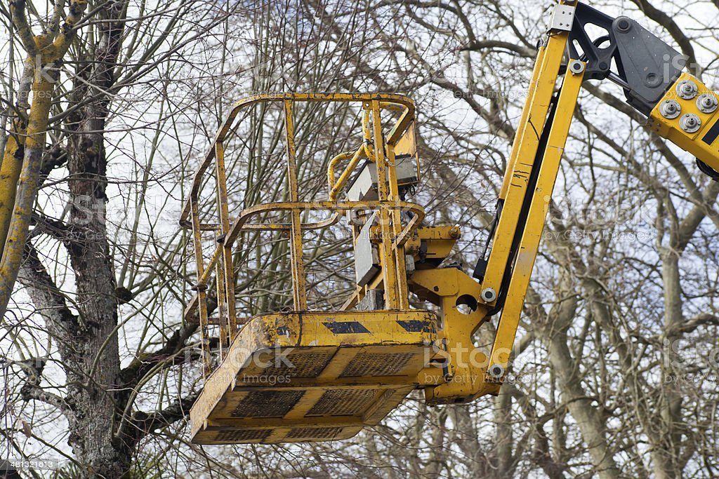 Cherry picker and leafless trees royalty-free stock photo