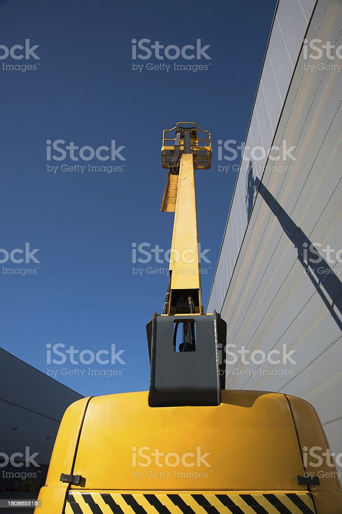 cherry picker elevated in front of a beige building royalty-free stock photo