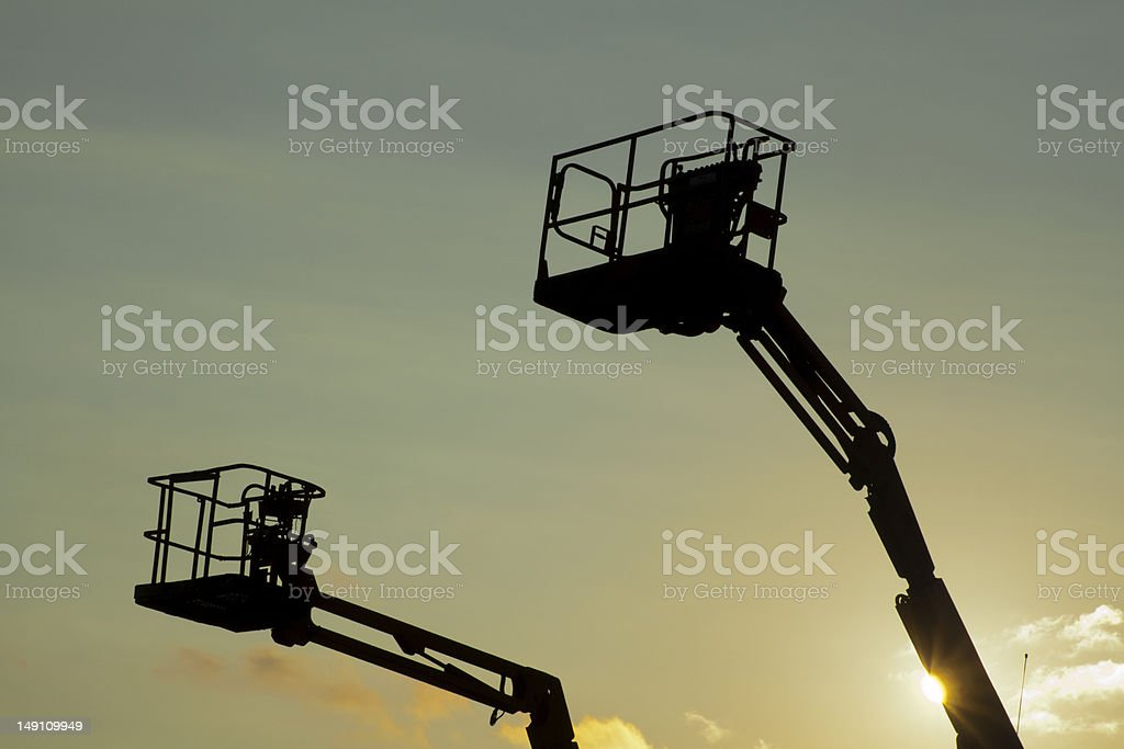 Cherry pickers at sunset. royalty-free stock photo