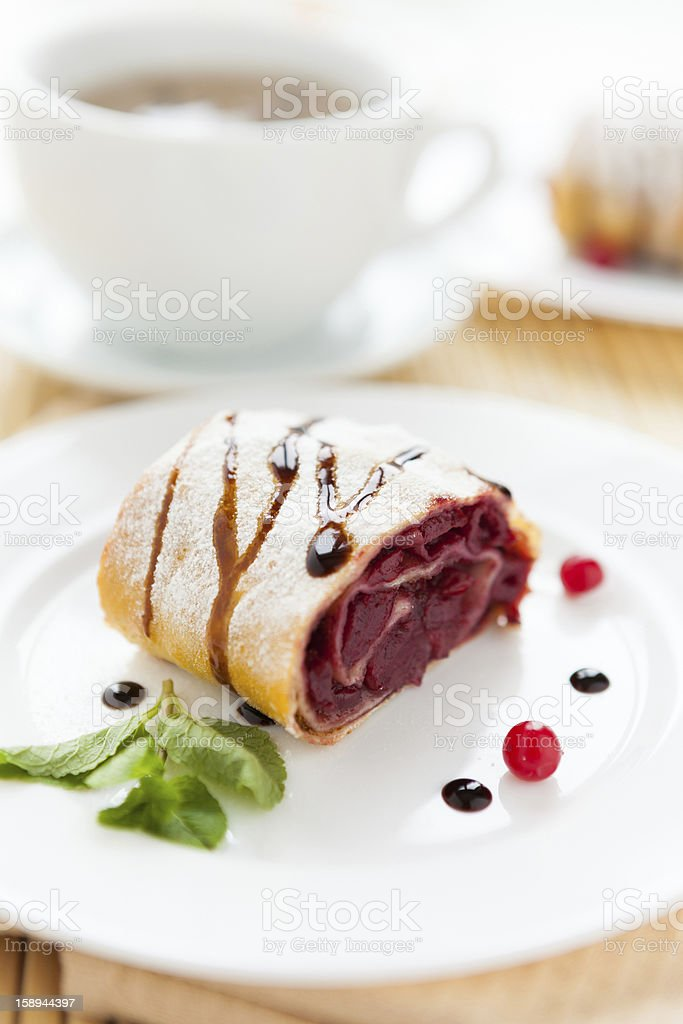 cherry strudel on white plate and a cup of tea royalty-free stock photo
