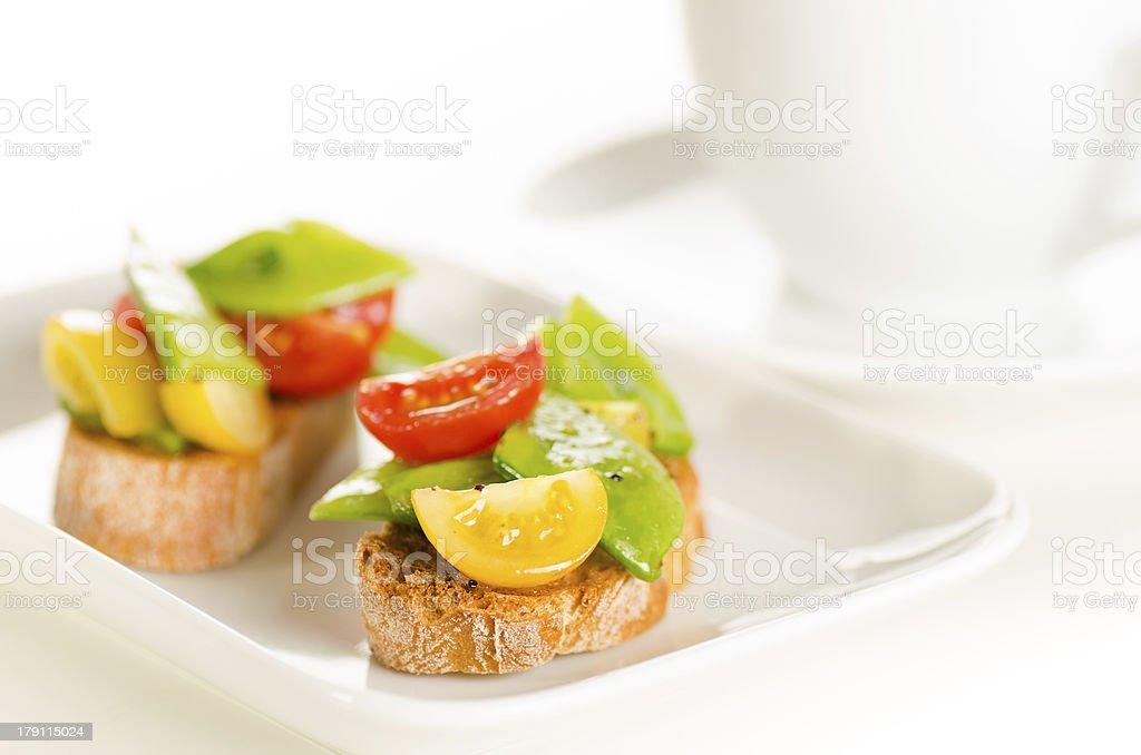 Cherry tomatoes and snow peas crostini royalty-free stock photo