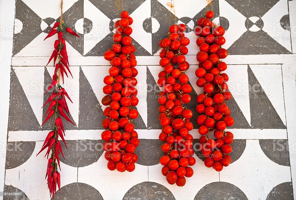 Cherry tomatoes are hanging on decorated wall, Chios island, Gre stock photo