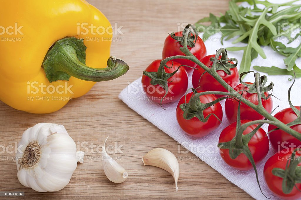 Cherry tomatoes bunch, arugula, garlic, yellow paprika, on board stock photo