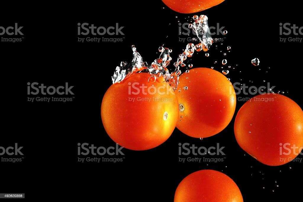 Cherry tomatoes falling into water at black background stock photo