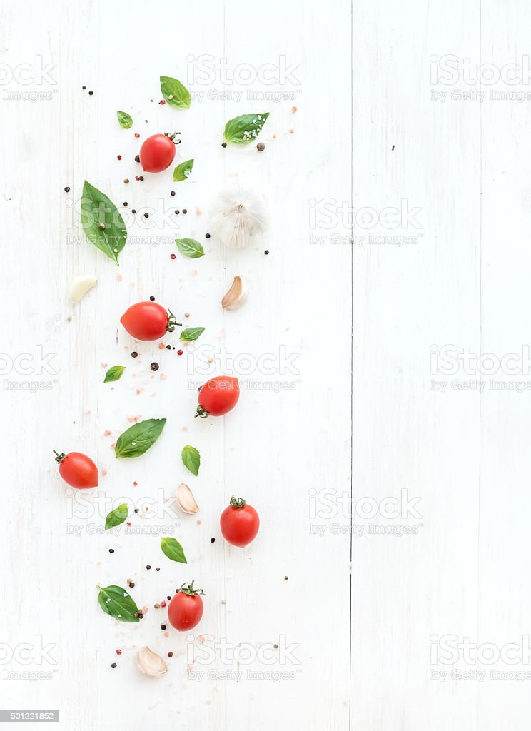 Cherry tomatoes, fresh basil leaves, garlic cloves and spices on stock photo