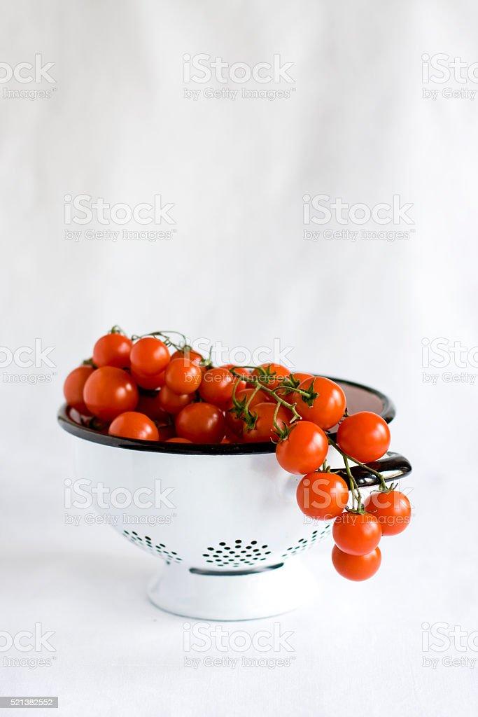cherry tomatoes in white strainer stock photo
