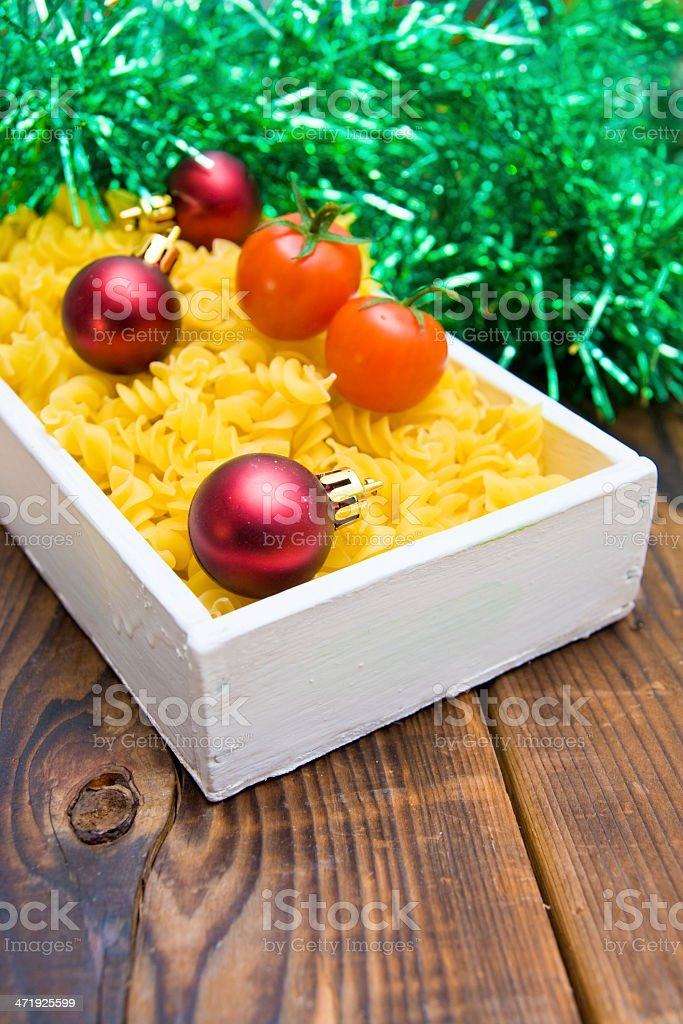 Cherry tomatoes, pasta, Christmas balls and tinsel on wooden background royalty-free stock photo