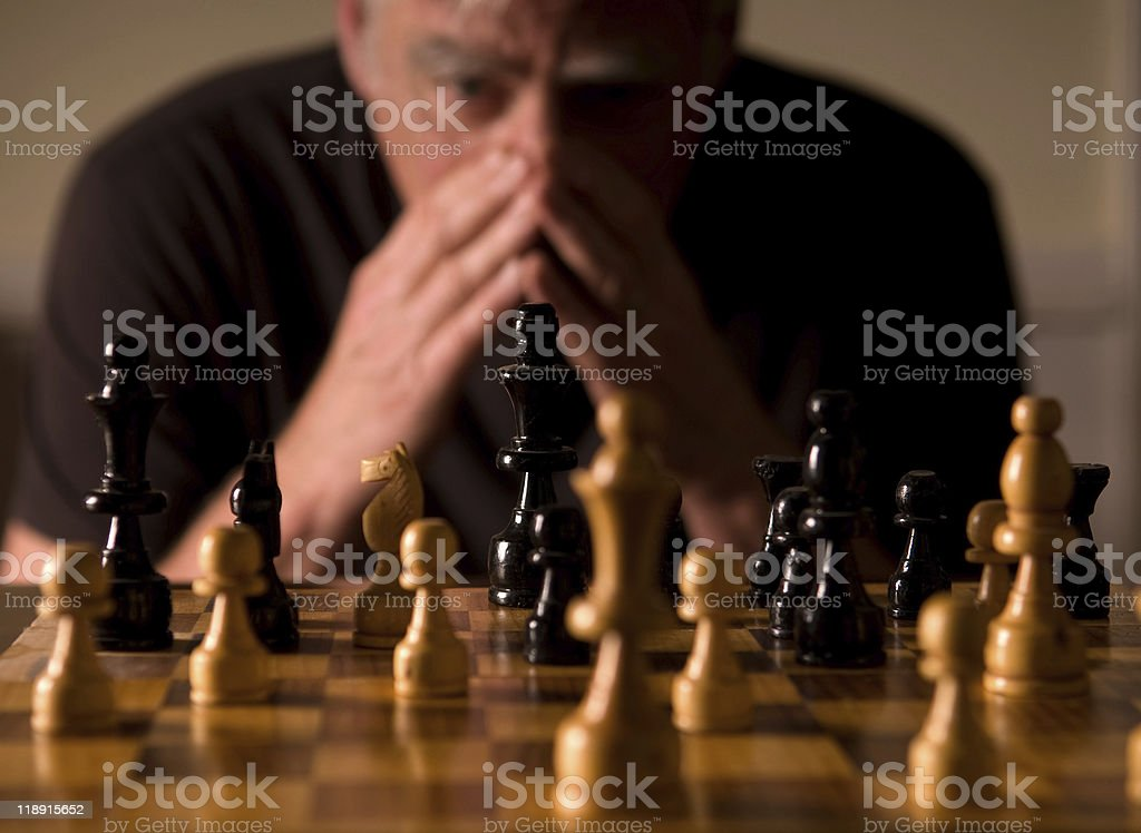Chess board with a concentrating man in the background royalty-free stock photo