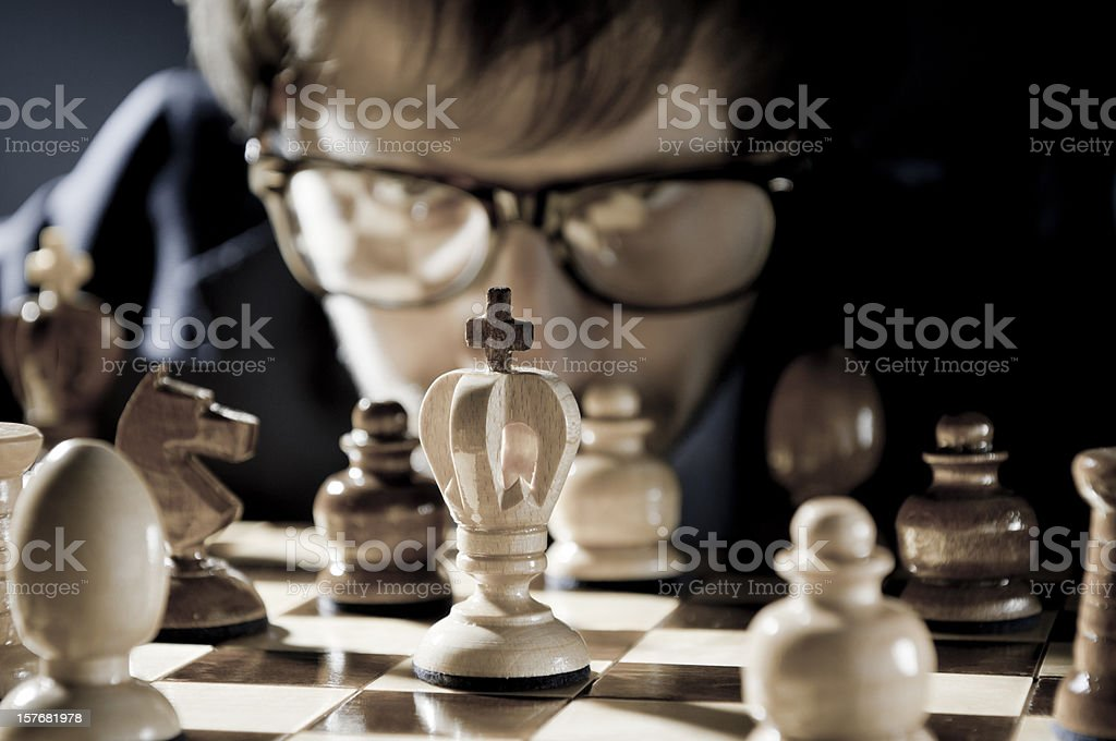 Chess competition, player in glasses thinking about next move stock photo