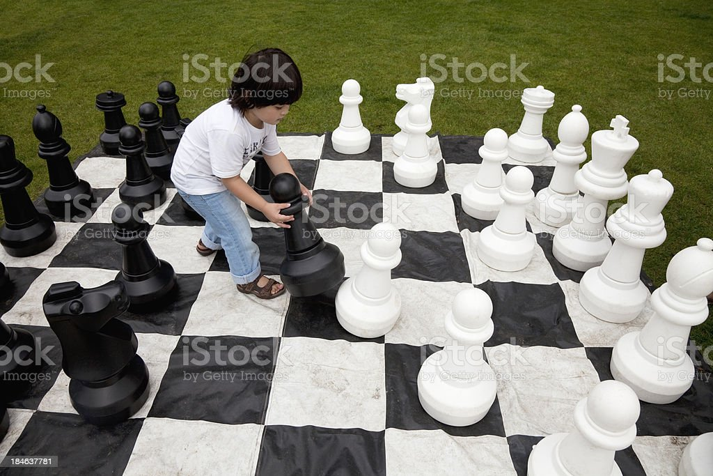 Chess, little boy makes his move royalty-free stock photo