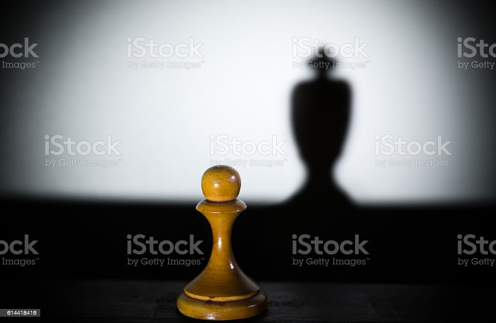 chess pawn casting a king piece shadow in dark stock photo