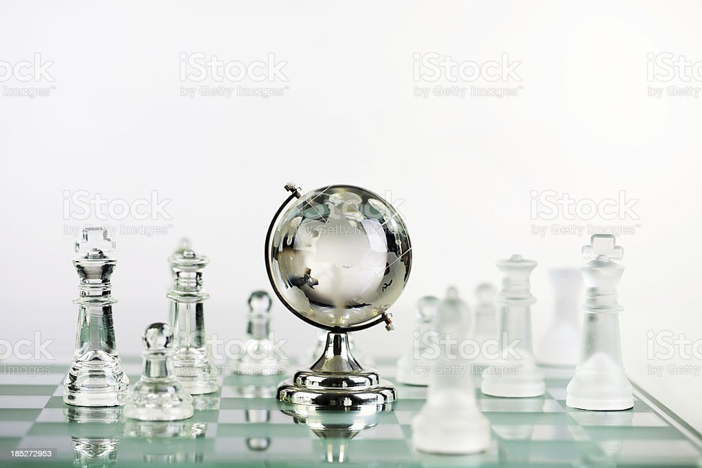 Chess pieces and glass earth globe. royalty-free stock photo